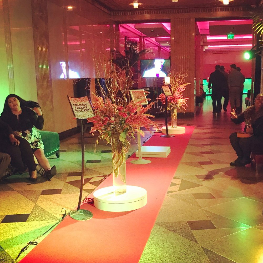 The red carpet with floral arrangements. Each platform displayed the name of the designer who showed their piece there.