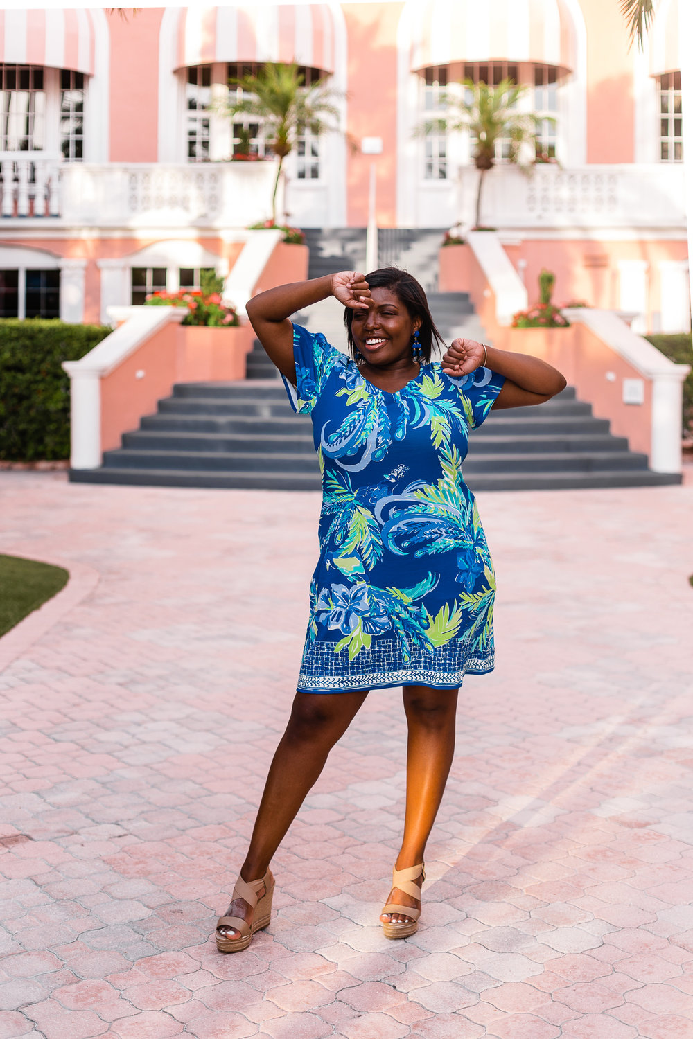 Tampa blogger Ayana Lage stands in front of the Don Cesar hotel in St. Petersburg, Florida. She is wearing a colorful Lilly Pulitzer blue and green dress.