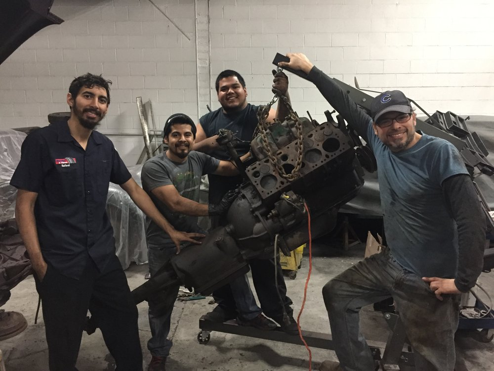 The original Automotive Mentoring Group that started the 1947 Cadillac project posing with the seized original flathead after pulling it from the car.  From the left, Rafael Franqui,  Edgar Lara, Jesus Gonzalez and Greg Alonzo
