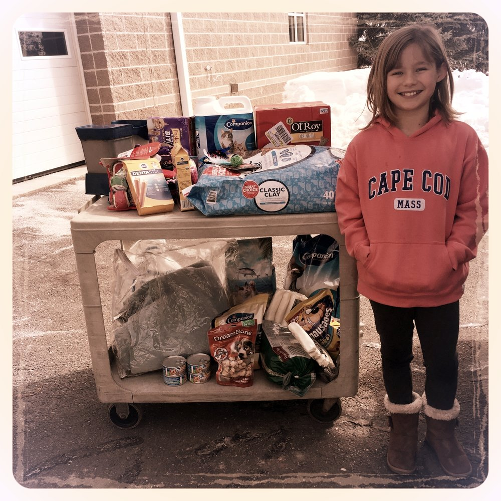 Kylie Scott from the 2007 girls team stands with animal food for a local animal shelter.