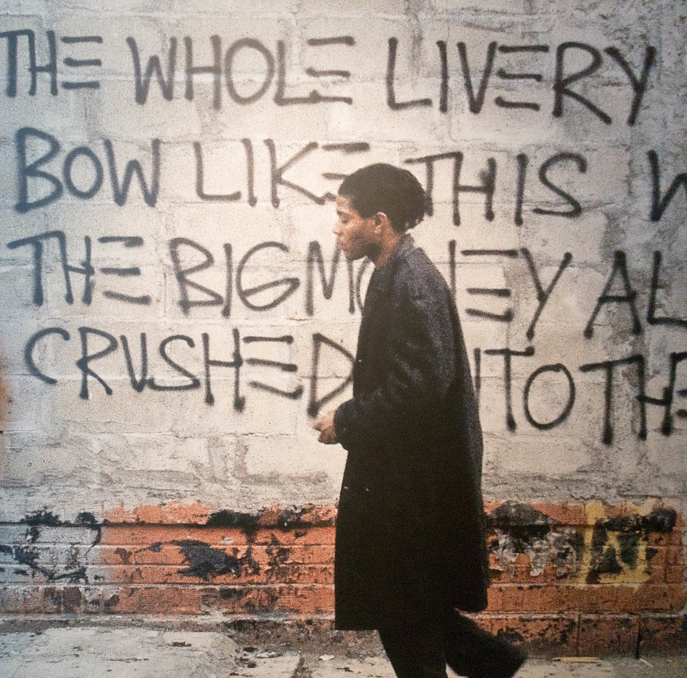 "Basquiat walking alongside his street graffiti, taken from the film ""downtown 81""."