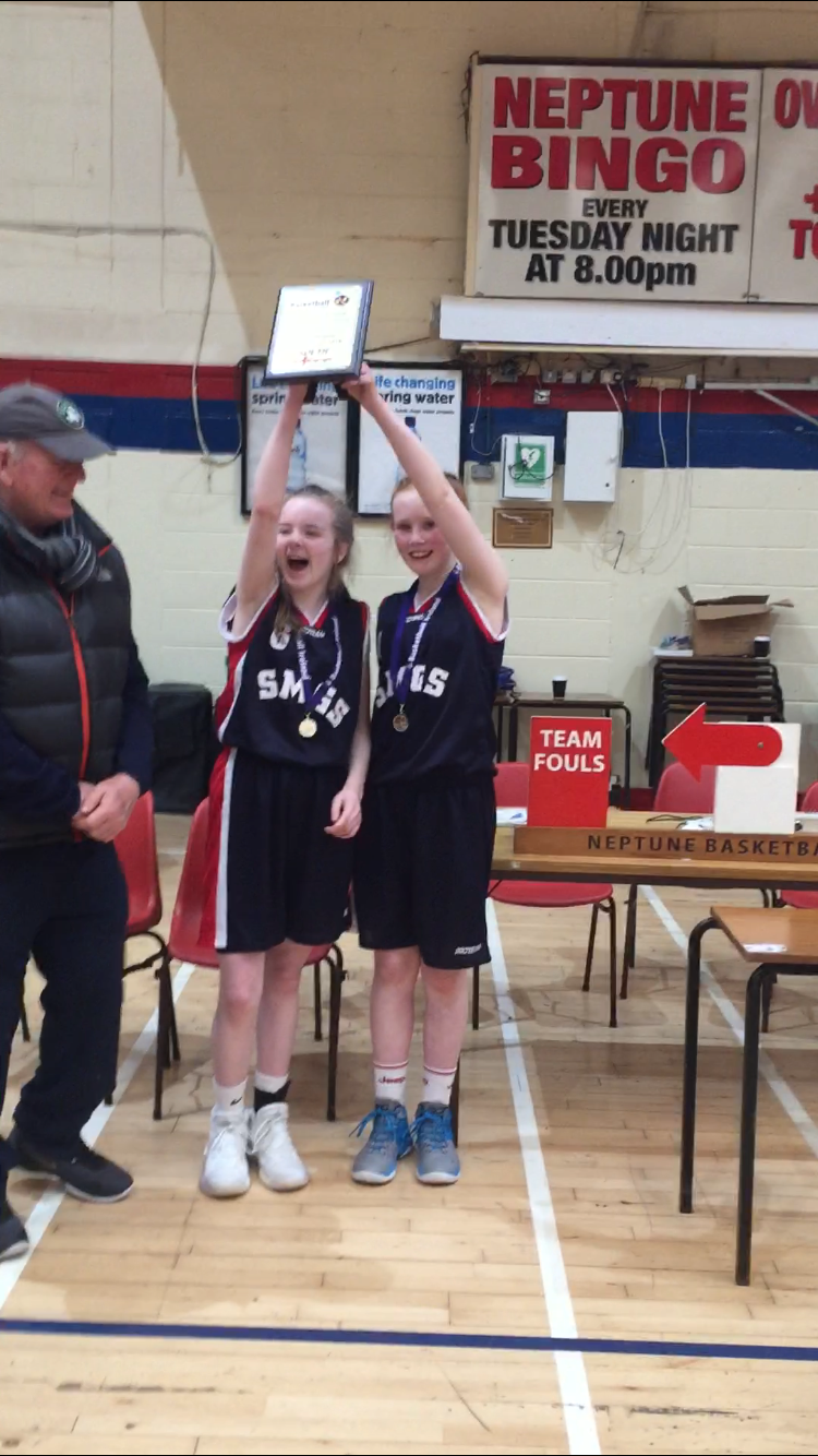Captains Saoirse Breen and Orla Humphreys lifting their plaque to their teammates