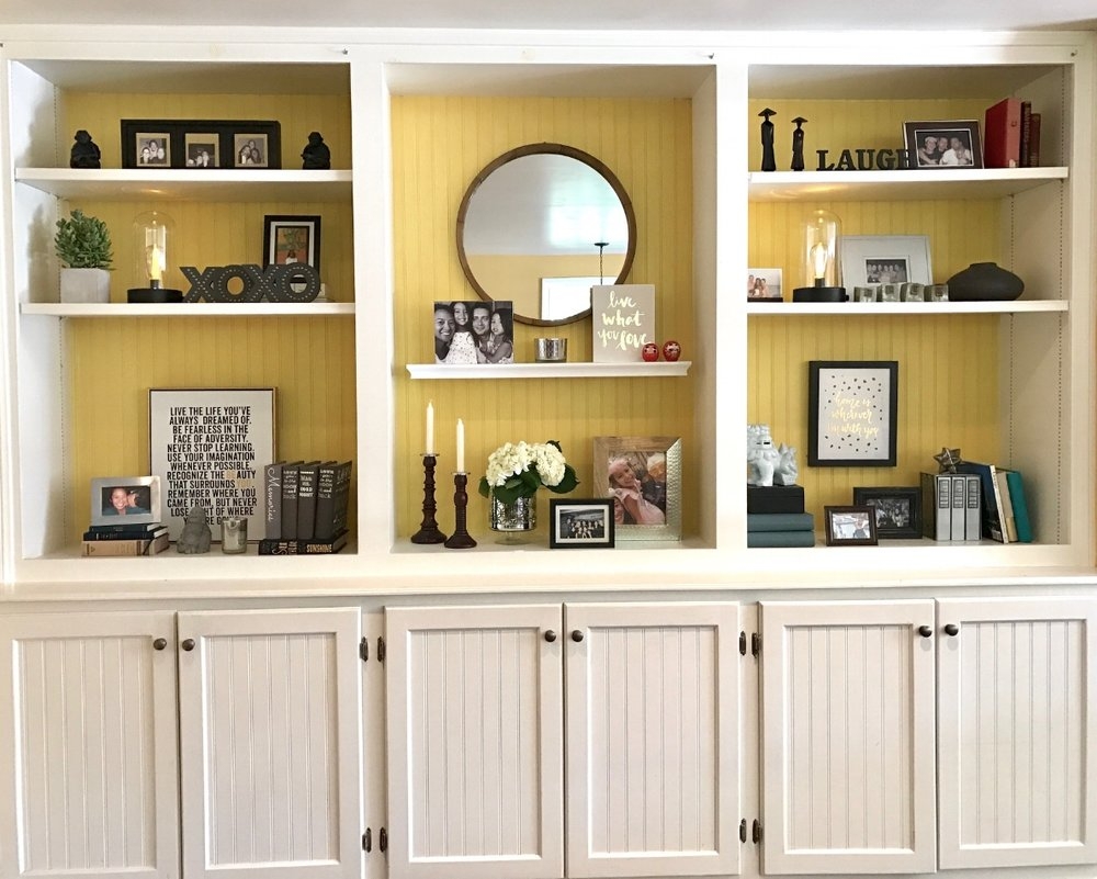 Ta-da! Styled built ins for displaying pictures and accessories.