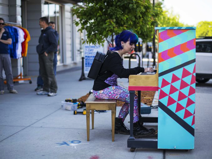 On her way to work in the East Village, Zoe Fey of Des Moines plays a piano being installed in front of RAYGUN for the City Sounds: Des Moines Public Piano Project. Photo by Rodney White/The Register