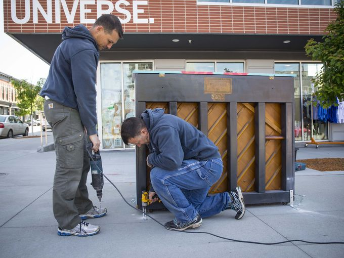 Andre Drost, left, and Vasile Zama, right, install a pianl in front of RAYGUN for the City Sounds: Des Moines Public Piano Project. Thursday May 19, 2016. Photo by Rodney White / The Register.