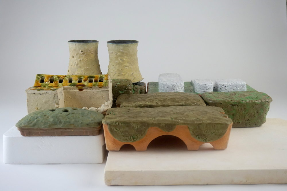 Cooling Tower Vases and Abandoned House Flower Brick - 24 x 19 x 10various reclaimed clays and slips, sink sludge, soft brick shards, waste and contaminated glazesBack:Cooling Tower VasesNuclear Power Plant Desk OrnamentPrivacy Hedge DoorstopMiddle: Abandoned House Flower BrickPrairie DoorstopTopiary DoorstopFront: Vacant Lot Bud VasePrairie Mantelpiece Decoration