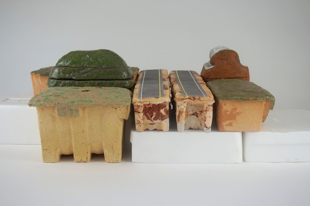 Landfill Butter Dish and Old Barn Doorstop - 20 x 15 x 8.5various waste clays, waste and contaminated glazes, unwanted stains, foaming enamelBack: Prairie Mantelpiece DecorationOld Barn DoorstopMiddle: Landfill Butter DishFront: Vacant Lot VaseTwo Lane Road CenterpiecePrairie Doorstop