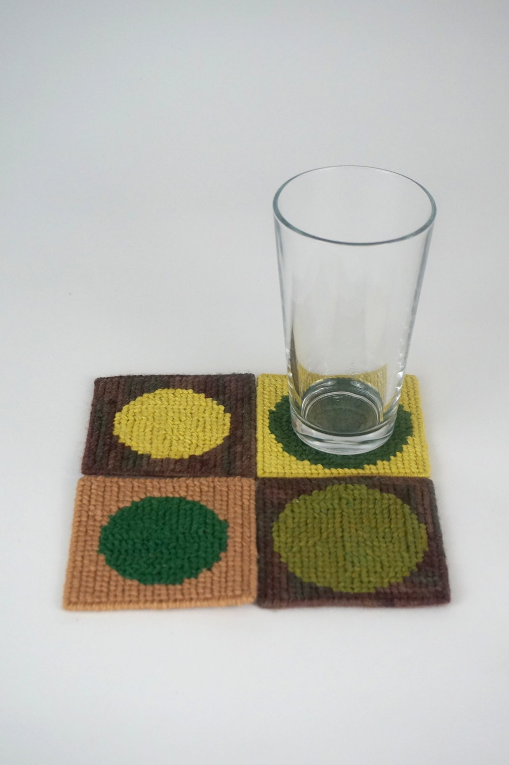 Irrigated Fields Coasters - 7.5 x 7.5salvaged plastic canvas and yarnCondensation drips from the glass and waters the fields.