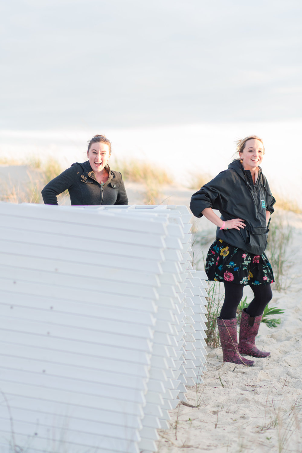 These are the faces of two girls carrying over a hundred chairs off a stormy beach and loving their job!