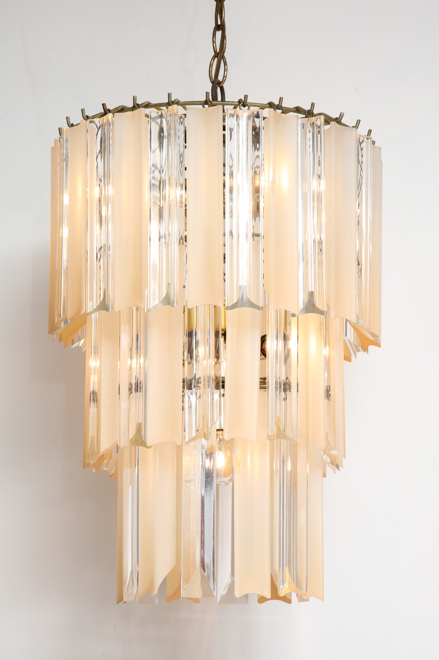 Camer chandelier with clear and peachy gold lucite triedre rods