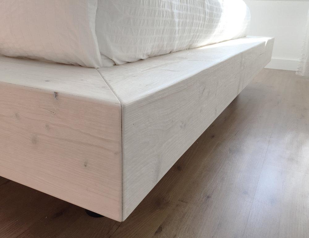Detail afbeelding van een geborsteld houten bed onderdeel.