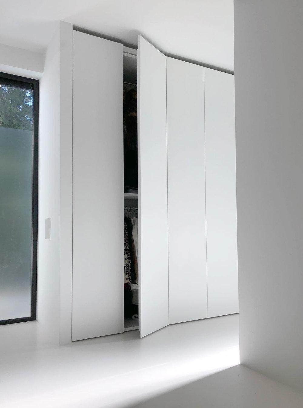 Afbeelding van een design kledingkast met een deur half open.