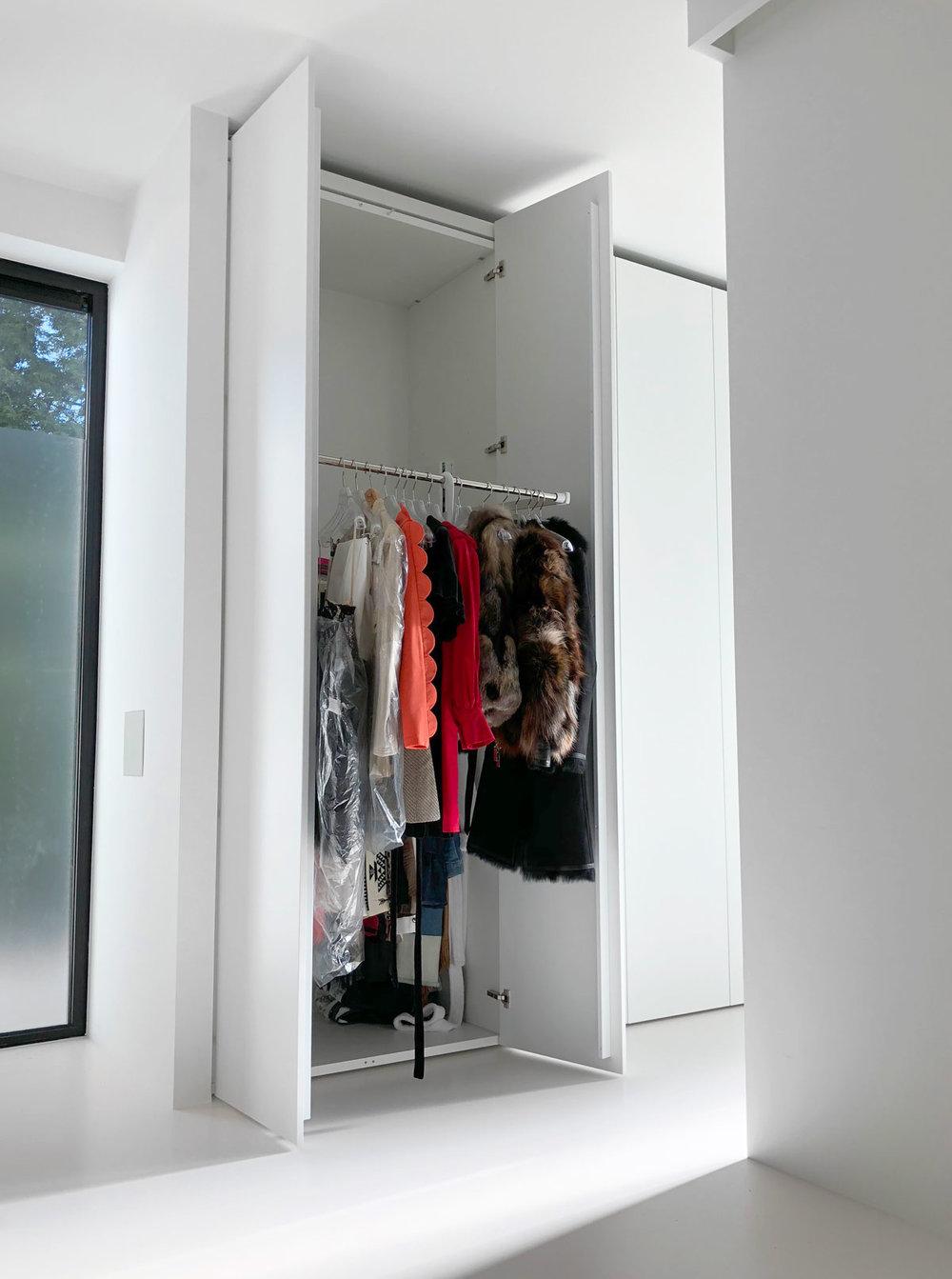 Afbeelding van een geopende kledingkast met een design kledinglift uitgeklapt.