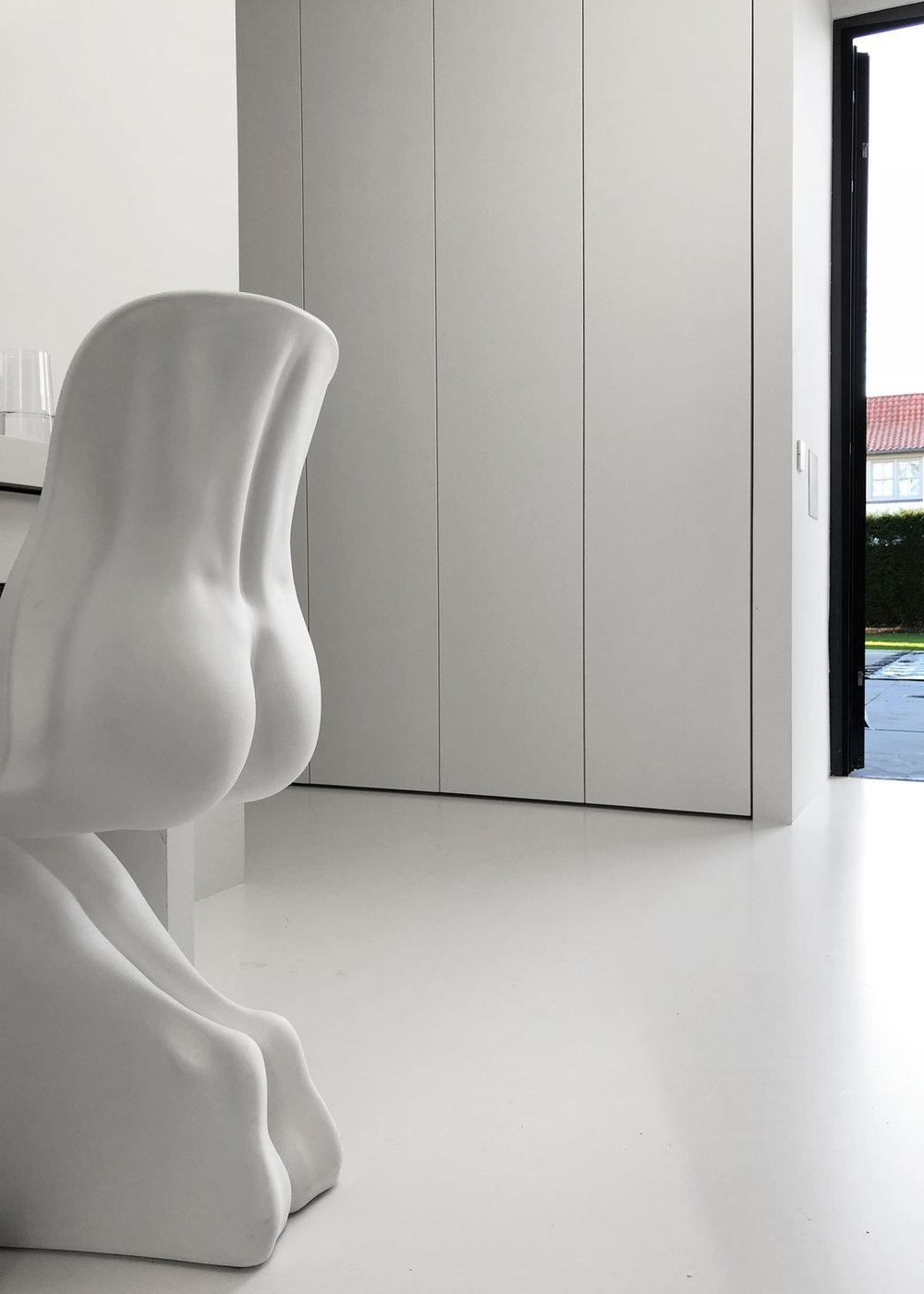 Afbeelding van een design kledingkast op maat met op de voorgrond een kunstwerk-stoel in de vorm van een vrouwenlichaam.