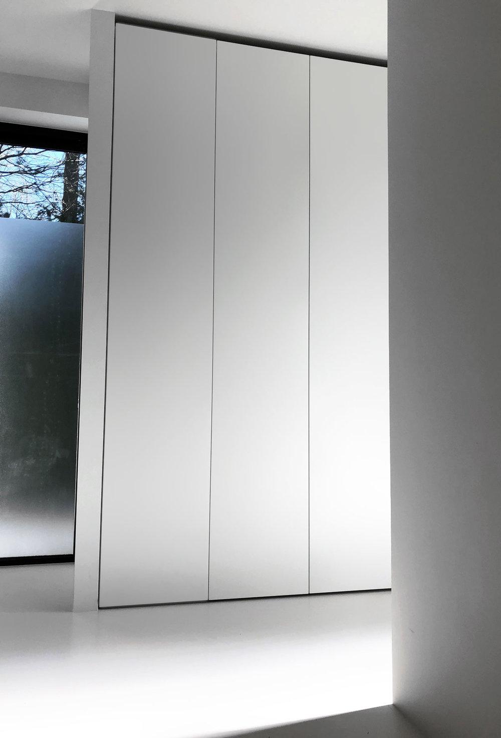 Afbeelding van een minimalistische design kledingkast op maat met handgreeploze deuren van vloer tot plafond.