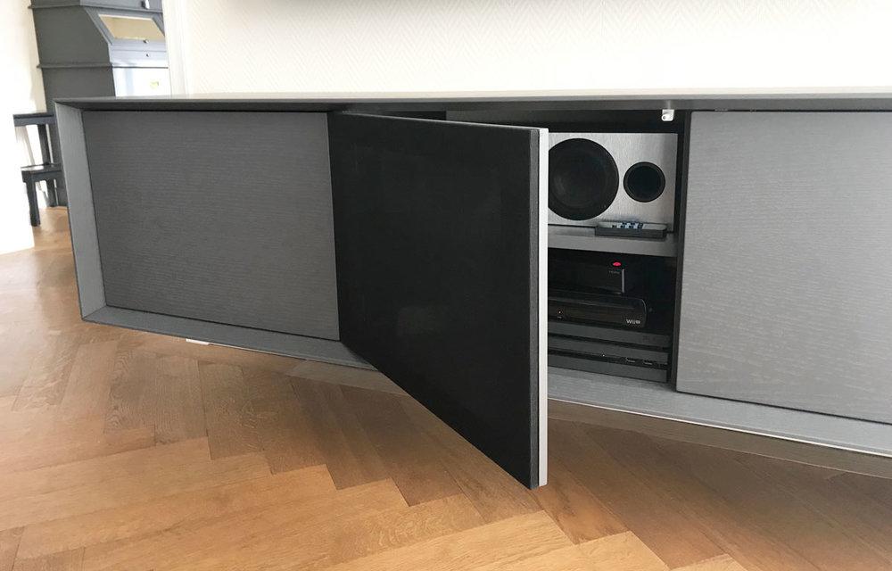 Afbeelding van een luidsprekerstof deur in een donker grijs TV meubel.