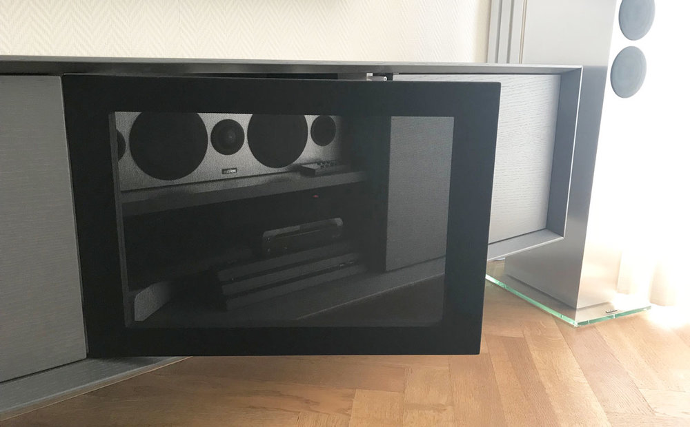 Afbeelding van een geopende luidsprekerstofdeur in een donker grijs TV meubel.