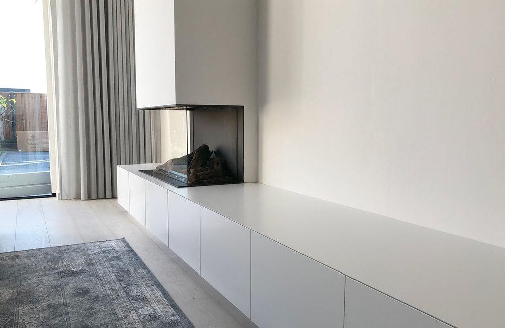 Afbeelding van een wit TV meubel op verstek met gashaard.