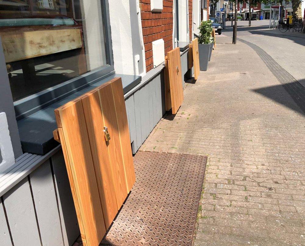 Een rij outdoor klaptafels voor een bar ingeklapt en met een hangslot afgesloten.
