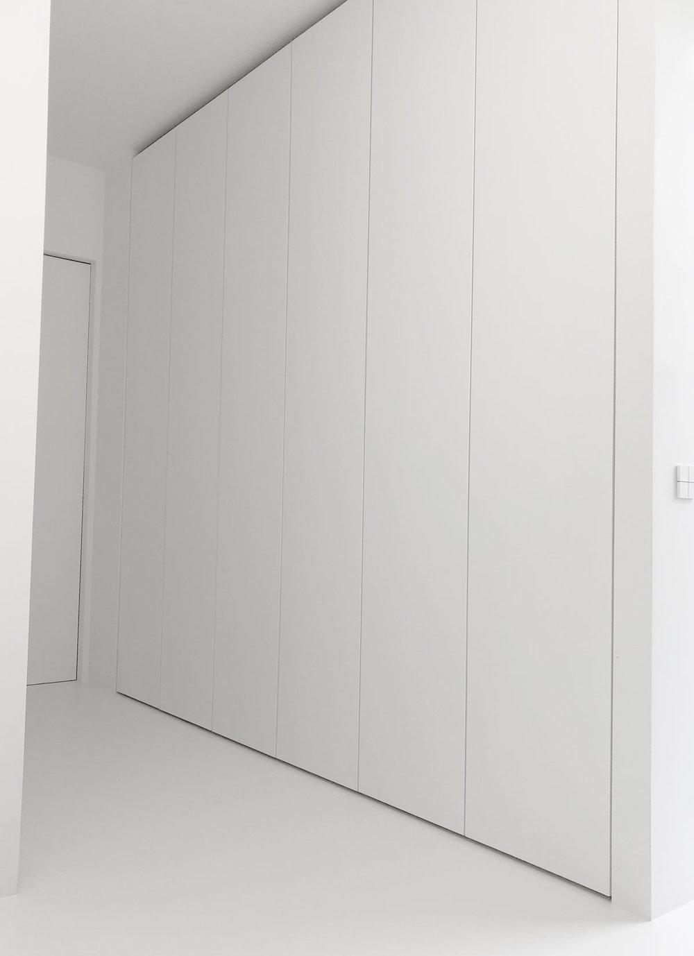 Afbeelding van een gang met aan weerszijden een design kledingkast op maat, de deuren zijn handgreeploos en push to open.