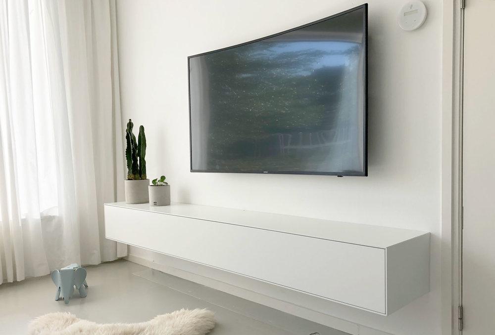 Afbeelding van een minimalistisch wit TV meubel en een curved OLED TV.