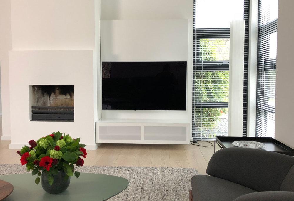 Afbeelding van voren genomen van een wandpaneel TV meubel in een modern interieur.
