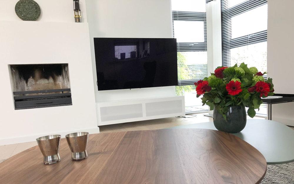 Afbeelding van een wandpaneel TV meubel gefotografeerd over een notenhouten salontafel.
