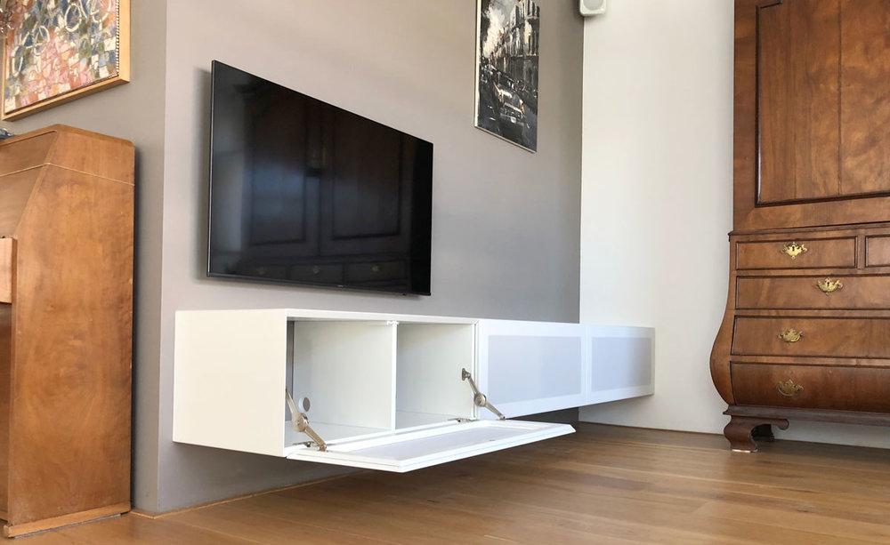 Afbeelding van een wit tv meubel op verstek met luidsprekerdeuren met een geopende klep.