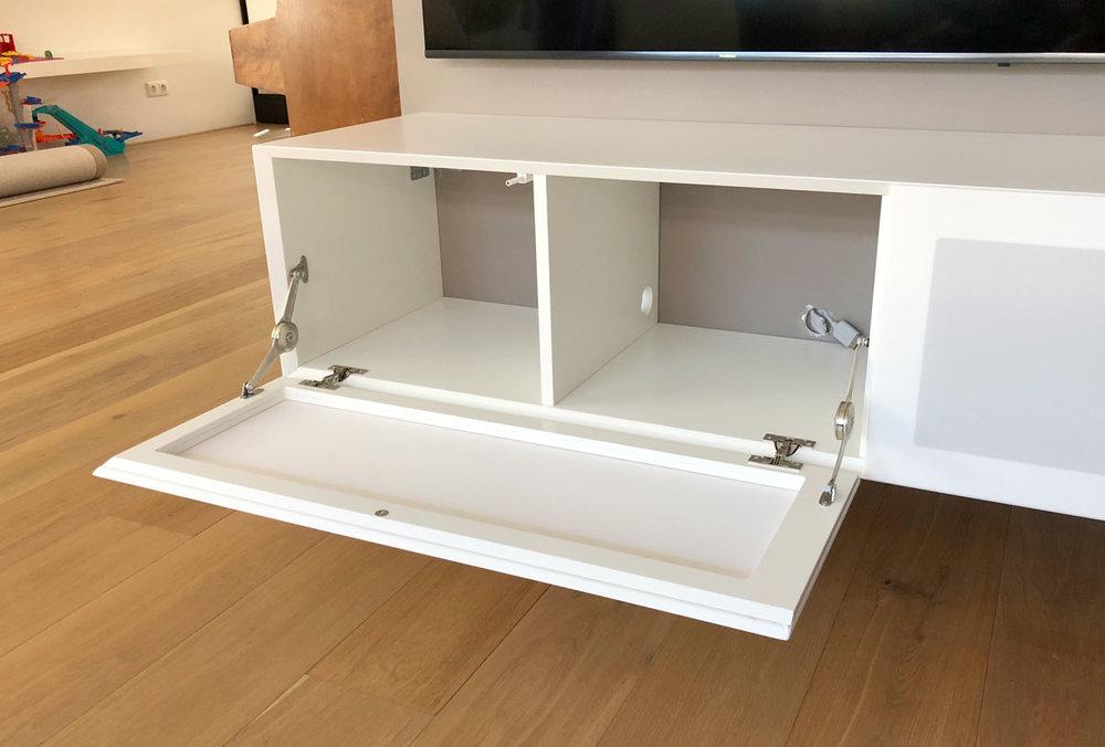 Afbeelding van een geopende luidsprekerklep in een wit design TV meubel.