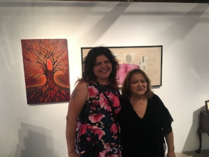 Daughter and mother Sandy Rodiriguez and Guadalupe Rodriguez stand in front of their paintings.