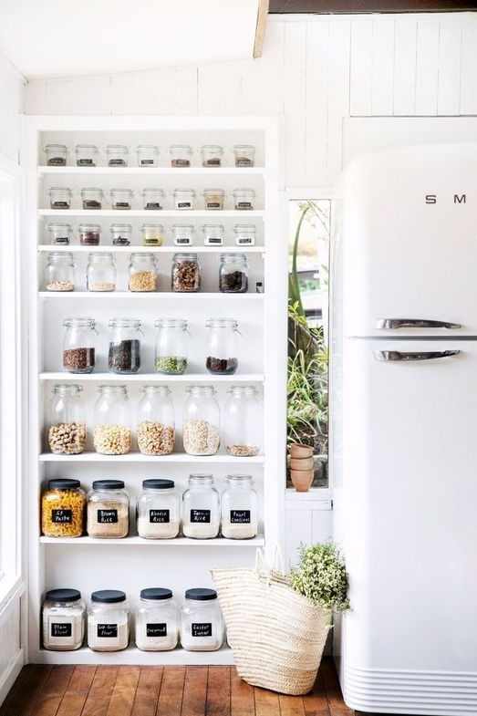 - Okay, if I'm being totally honest, my favourite thing about this image is the fridge. I would love to have a Smeg fridge some day, but it may just be a pipe dream. Onto the pantry. It's a bit more out in the open, which makes me love its minimalist vibes even more. Our jars are two rows deep on our open shelves because they're only as tall as our cabinets, but this is the dream. I love how they're all perfectly spaced and smallest to biggest going down the shelves.