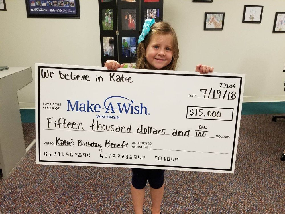 Katie's Daughter, Gracie proudly presenting the check to make-a-wish wisconsin.