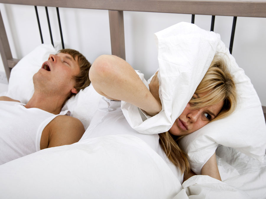 Woman covering her ears as partner snores in bed