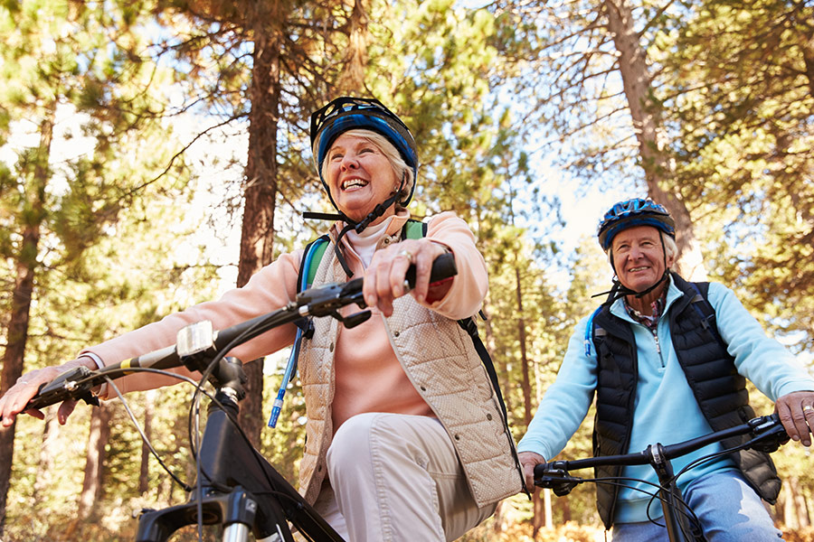 Older couple riding their bikes in nature