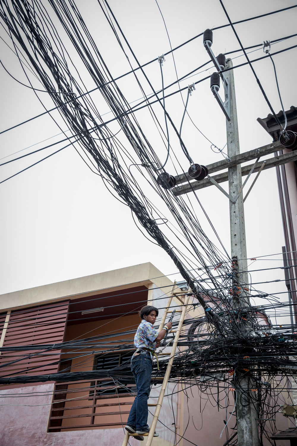 Men work on cables that hang over shops, hotels, and homes.