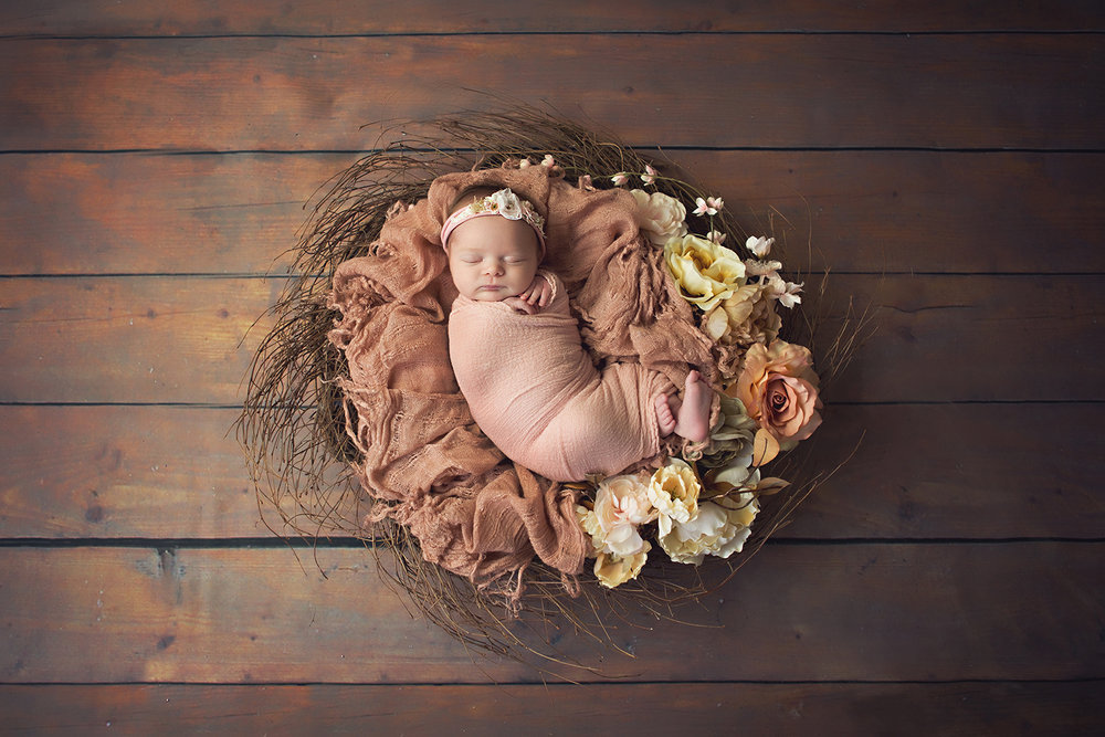 Newborn baby girl in rustic floral design