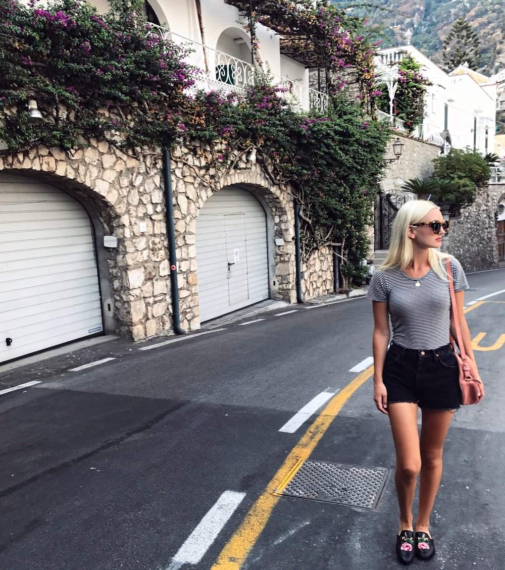 WALKING THE STREETS OF POSITANO WEARING  REFORMATION TEE ,  PALMA BAG ,  GUCCI LOAFERS  &  WRANGLE SHORTS
