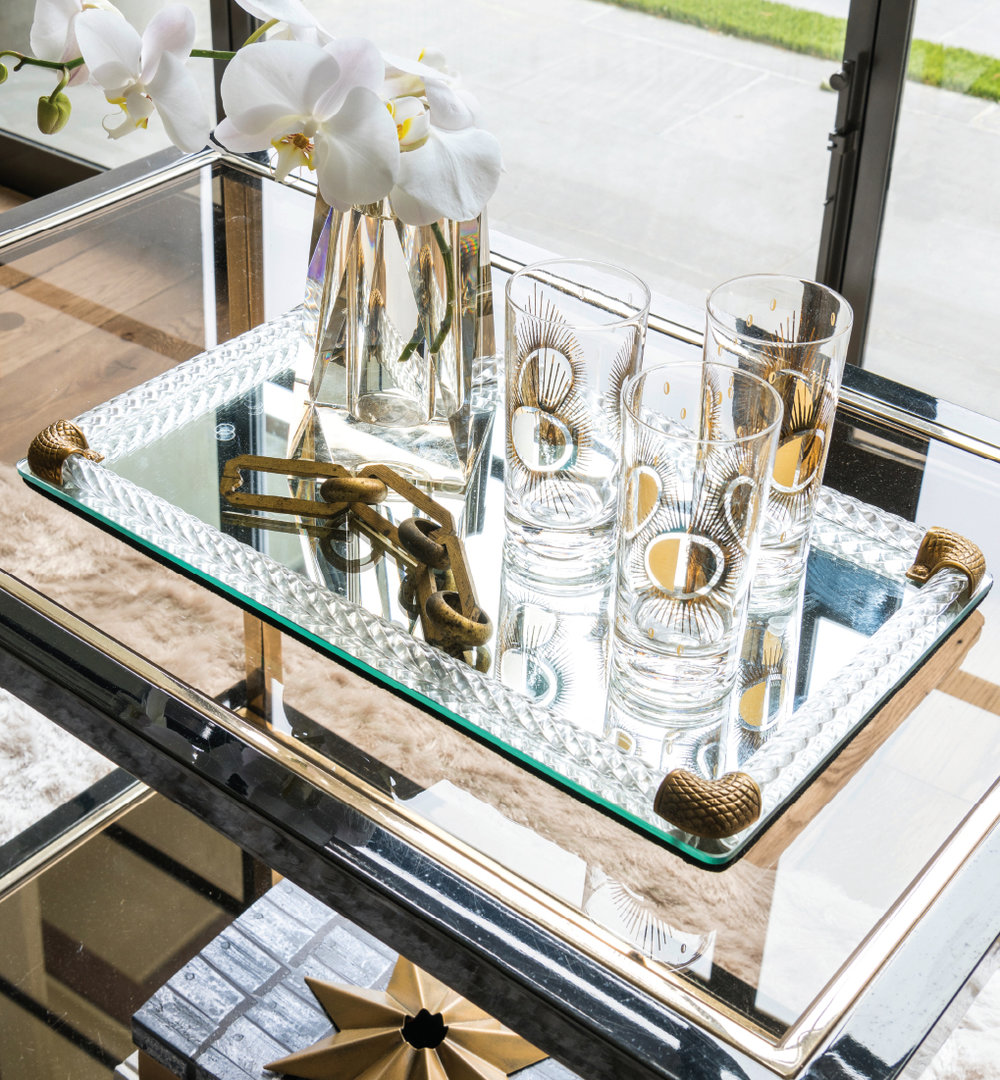 Vintage barware and bar cart mixed on modern day tray invites your guests to relaxin in your home. Photo by Michael Hunter