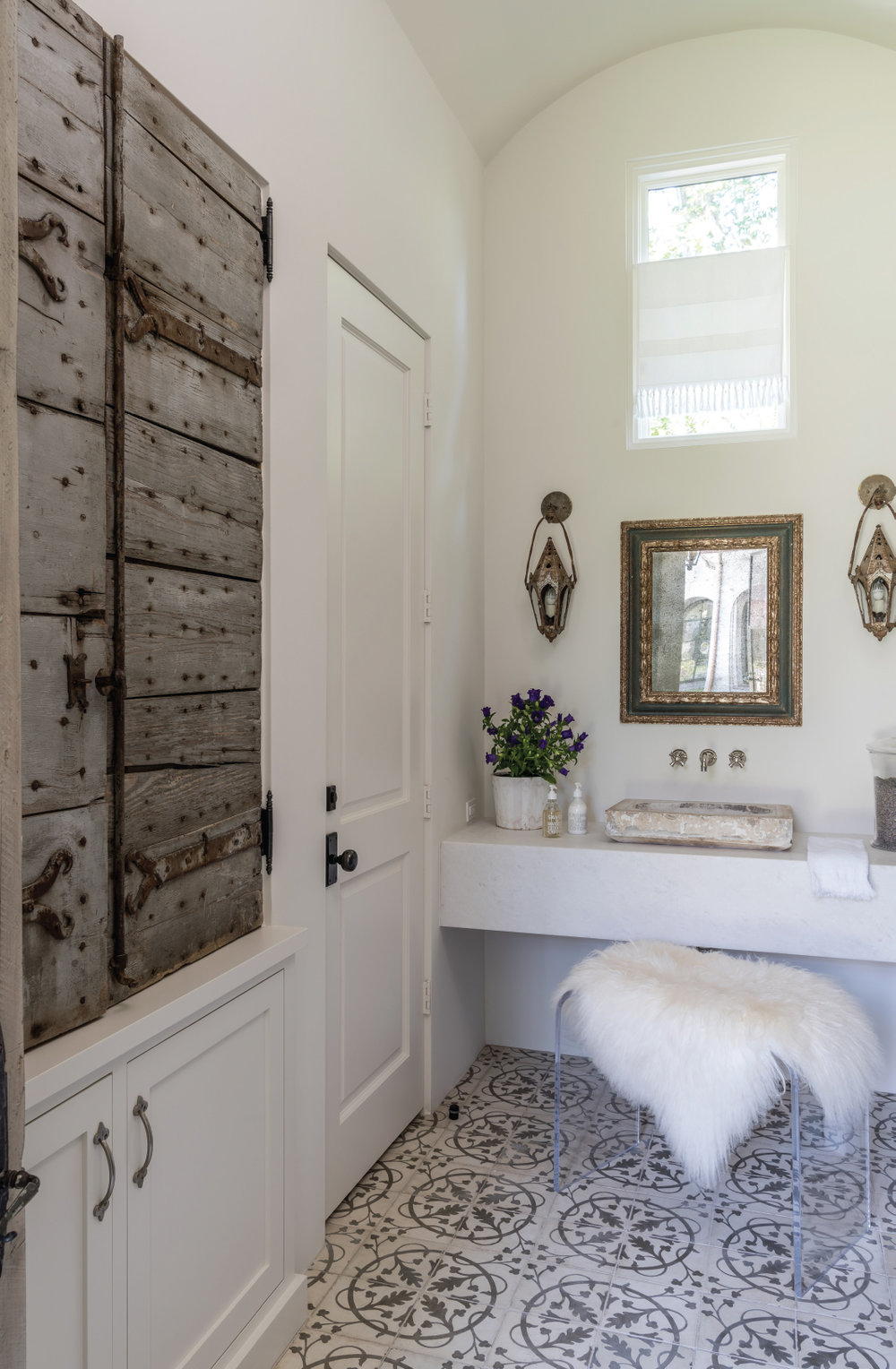 The fusion of antique doors from Round Top, reclaimed floor tile and sink paired with a modern bench and clean lined vanity is a perfect recipe for the mixology of design. Photo by Michael Hunter