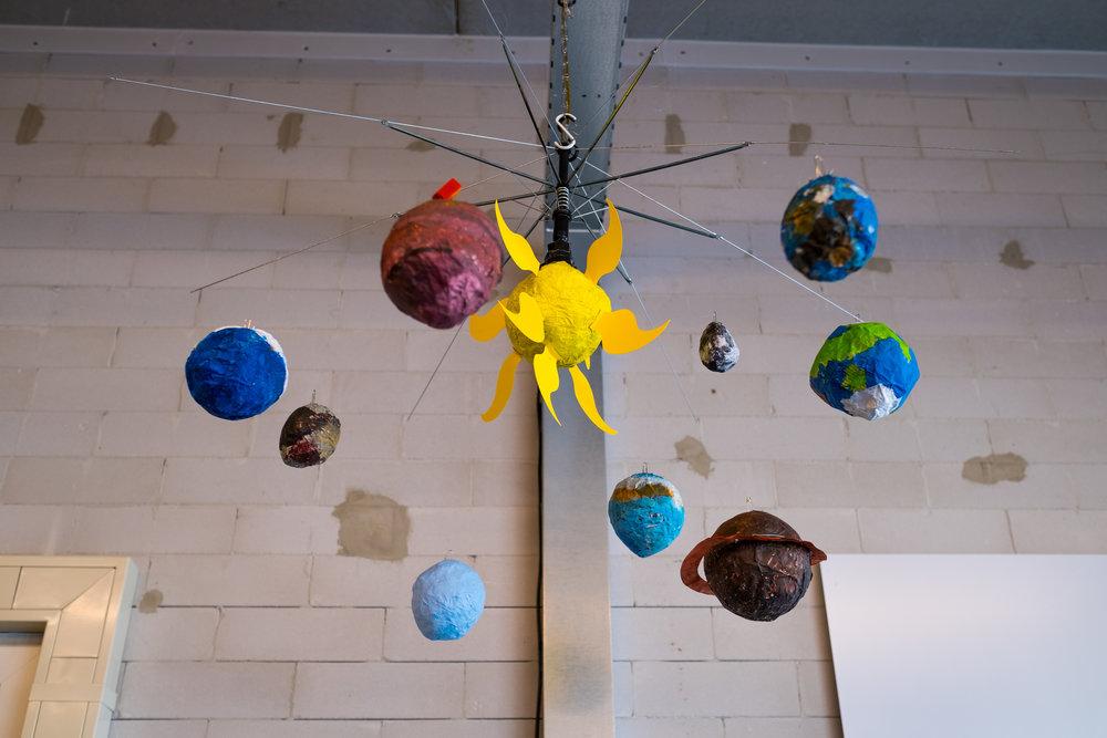 """Het planetenstelsel  Aya: """"Met de hele groep hebben we een planetenstelsel gemaakt. De takken waar ze aanhangen zijn gemaakt van een oude paraplu. Ik heb Saturnus ontworpen, en Fatima heeft Pluto gemaakt."""""""