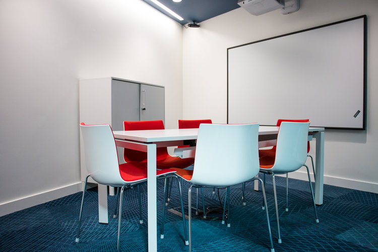 A small meeting room with a whiteboard and tables and chairs