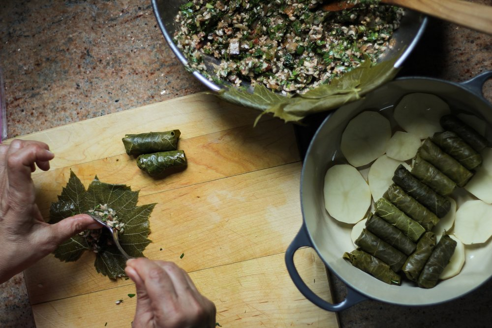 My mom making vegan stuffed grape leaves