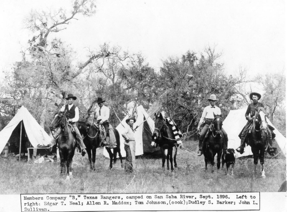 """Infamous Pecos County Sheriff """"Dud"""" Barker (third horseman from the left in the bow tie) while a Texas Ranger under the command of Captain Bill McDonald.  Barker later went on to become Pecos County Sheriff, a post he held from 1904 to 1926 while living in the Old Jail with his family. He was known for his strict enforcement of Prohibition, a stance which irritated many Pecos County citizens, but to which he replied, """"I don't make the laws, I just enforce them."""" Barker and his family lived in the Pecos County Jail during his term, which had living quarters for this purpose.  Pecos County historian Olan George recalled that during Barker's time as sheriff, the front yard of the old jail was his pride and joy. Back then the prisoners could be used for work, so the sheriff spent many hours along with his prisoners doing yard work. """"Had there been such an award back then, the old jail with its grass, hedges, flowers and trees would have been chosen Yard of the Month.""""  Sheriff """"Dud"""" Barker was drafted into the sheriff's office. After the assassination of Sheriff A.J. Royal at his desk (a killing that was never solved) a group of Fort Stockton's political leaders visited with Barker and asked that he run for sheriff in the 1904 election. According to Roland Warnock, this citizens' group first approached the Texas Rangers to inquire about someone who could straighten out things in their town. """"I have a man,"""" replied the Ranger captain, """"But I have to tell you that if you make him your sheriff, he'll BE your sheriff.""""  """"That's what we want,"""" replied the group. """"Someone who will put an end to all of this monkey business.""""  Little did they know how prophetic that Ranger captain's words would become.  Barker began his 22-year tenure on January 1, 1905, and according to long-time resident and historian Olan George,one of the first things Barker did was spy on a poker game being played by the town's prominent citizens. Because gambling was against the law, he visited each of th"""