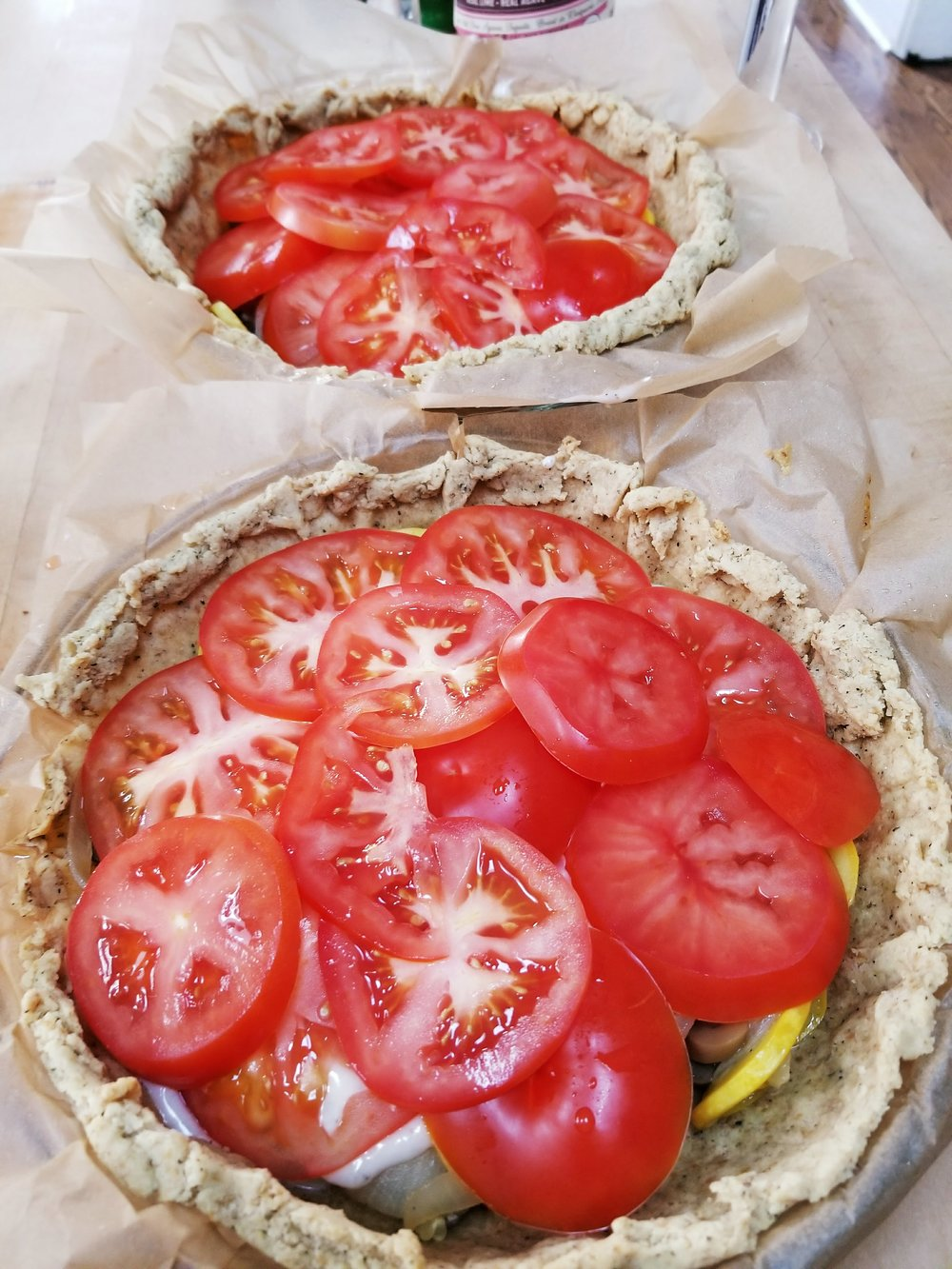 Layer two tomatoes to each pie on top of the sauce layer.