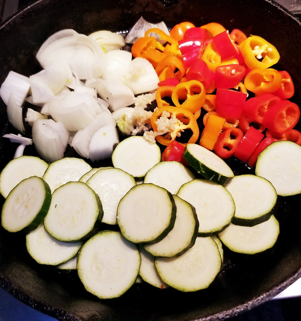 Drizzle olive oil on the bottom of a large frying pan or pot on Medium heat and place your onion, peppers, zucchini, and garlic until they get tender. Add in a tsp of Italian dried herbs as its cooking.