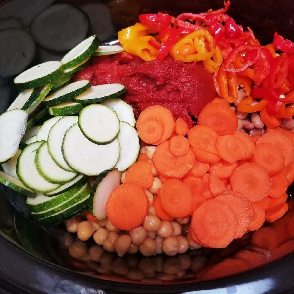 Place the tomato paste, carrot, sweet peppers, and zucchini in the crock pot.