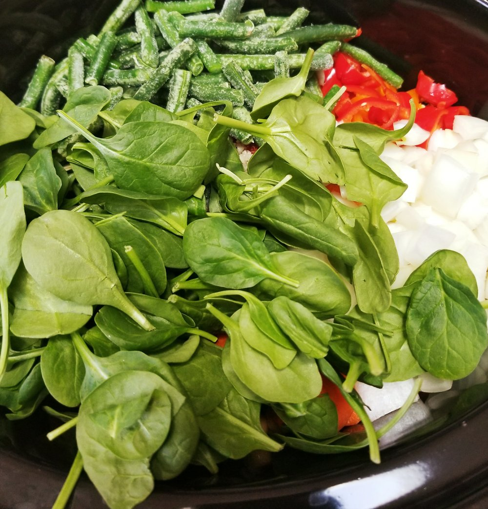 Add in your garlic, onion, green beans, and spinach to the crock pot.