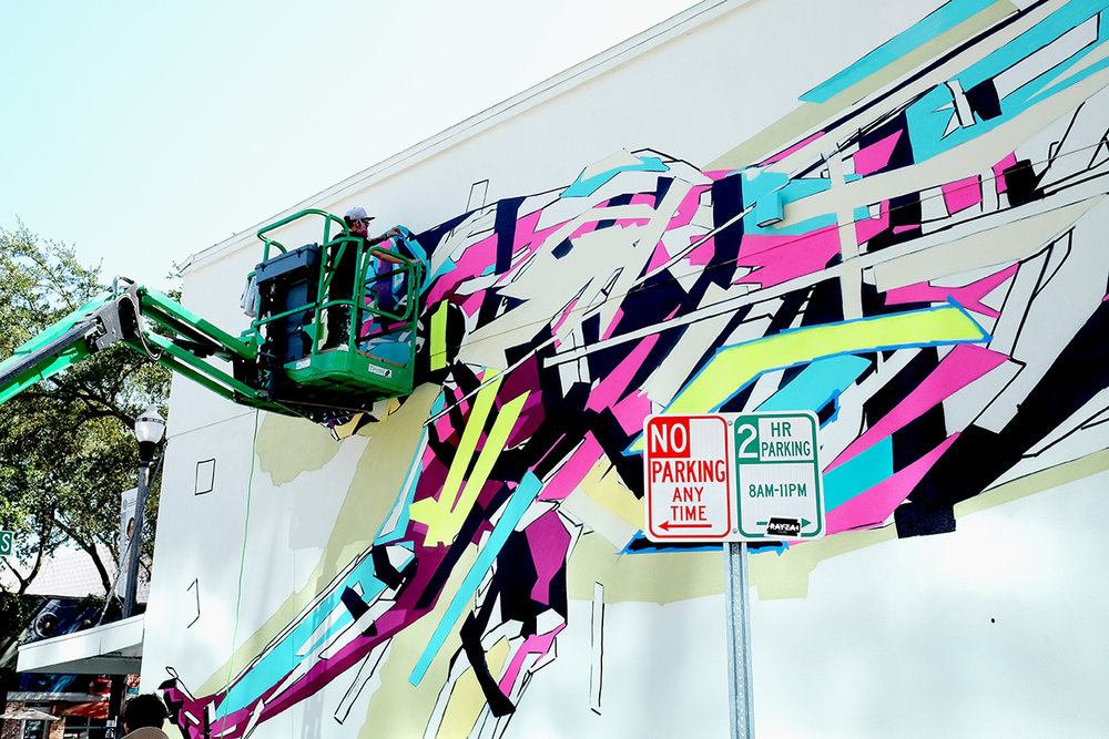 "A mural artist paints during St. Pete's ""Shine on"" festival. Heather Comparetto/The Penny Hoarder"