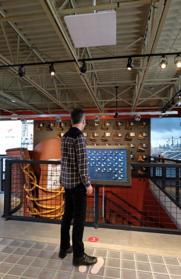 Guided by shoe prints on the floor, a man views the Red Wing Shoe's  Wall of Honor