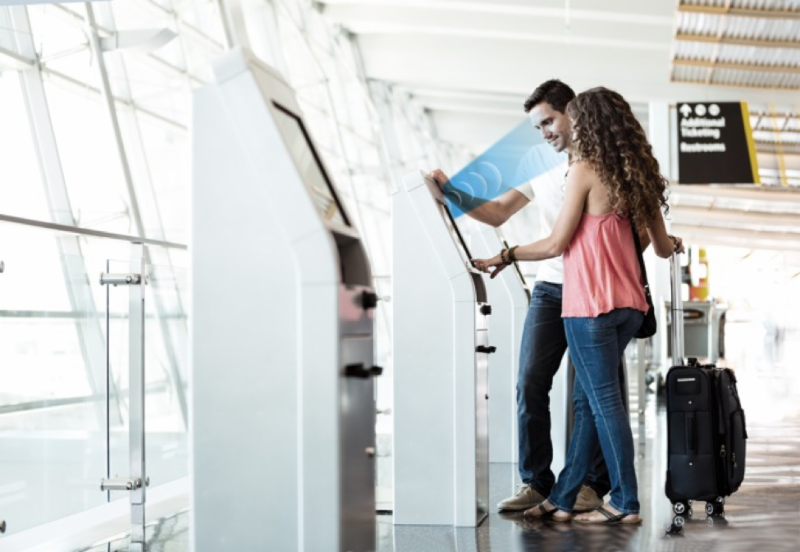 Passengers receive boarding passes at a kiosk that features Audio Spotlight technology